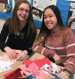 two students making valentines