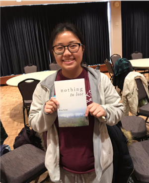 student poses with speakers book